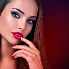 Woman with dark brown eye makeup and bright red lips and nails