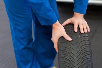 Mechanic rolling a tire wheel