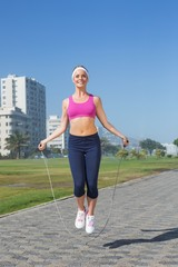 Fit blonde skipping rope on the pier