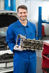 Smiling mechanic holding an engine