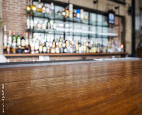 Tuinposter Alcohol Top wooden table with Bar Blurred Background