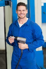 Smiling mechanic holding power drill