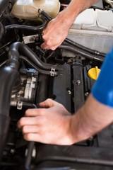 Mechanic examining under hood of car