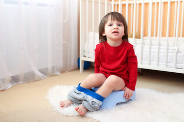 little boy sitting on potty at home
