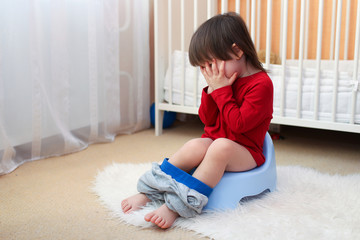 crying toddler sitting on potty at home