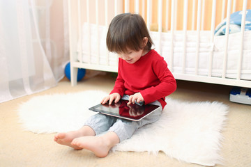 lovely 2 years boy in red shirt with tablet computer