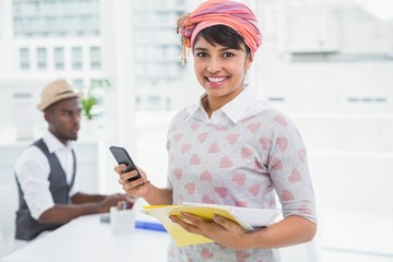 Casual businesswoman smiling and using phone