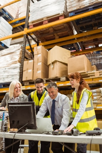 Warehouse team working together on laptop - 76896386