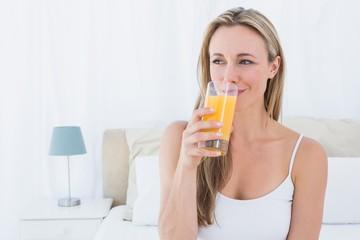 Smiling blonde drinking glass of orange juice