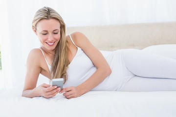 Smiling blonde using her smartphone on bed