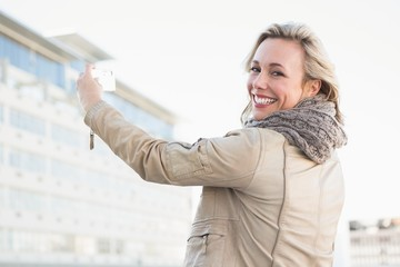 Cheerful blonde with mobile phone and looking at camera
