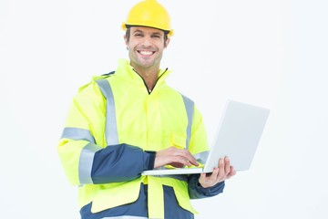 Male architect in reflective clothing using laptop