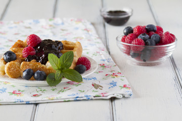 Waffles with blueberries, raspberries, jam and a sprig of mint