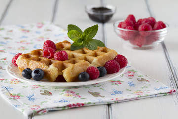 Waffles with blueberries, raspberries and a sprig of mint