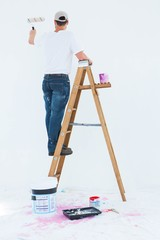 Man on ladder painting with roller