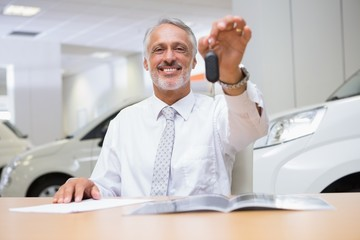 Smiling salesman giving a customer car keys