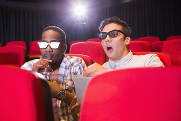 Astonished young friends watching 3d film