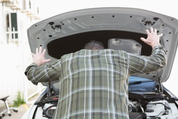Angry man checking his car engine after breaking down