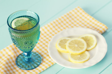Blue crystal goblet and a white plate with slices of lemon