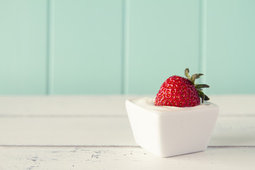 A strawberry with greek yogurt over a white wooden table