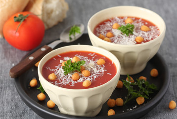 Fresh tomato soup with parmesan and croutons in a white bowl