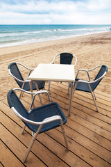 Wooden floor and metal armchairs on the sandy beach