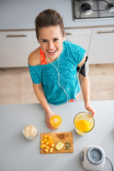 Portrait of happy fitness young woman making pumpkin smoothie