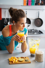 Fitness young woman with glass of pumpkin smoothie in kitchen