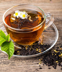 Glass Cup Tea with camomile flower and Mint Leaf, on brown woode