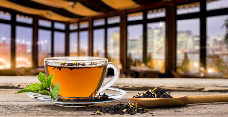 Glass Cup Tea with Mint Leaf, in evening cafe