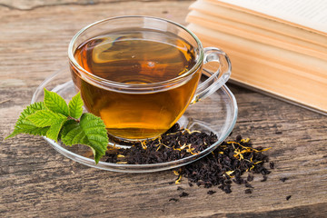 Glass Cup Tea with and Mint Leaf, on brown wooden palette