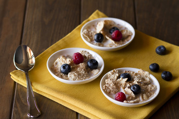 Three white bowls with cereals, raspberries and blueberries