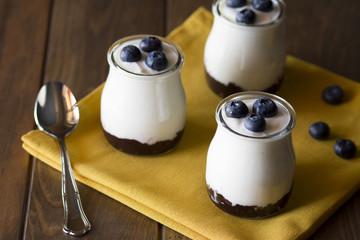 Three jars with greek yogurt, blueberries and jam. Vintage look.