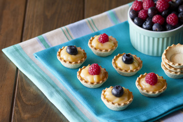 A platter with several blueberry and raspberry tartlets