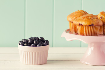Blueberry muffin in a cakestand and several blueberries. Vintage