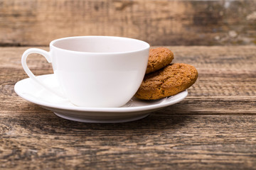 Ivory tea cup with sweet cookie on wooden palette