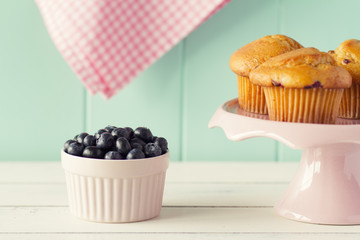 Blueberry muffin on a cakestand and several fresh blueberries.