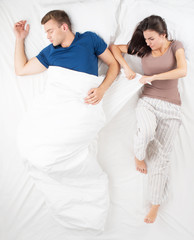 Young couple dividing a blanket while sleeping
