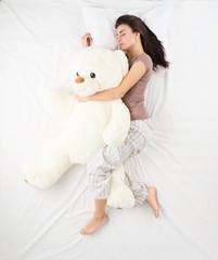Woman sleeping with large teddy bear
