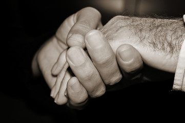 young man holding the hand of an old man, in black and white