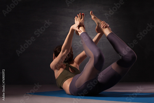 Poster Young woman practicing yoga in bow pose