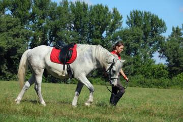 Groom girl with race horse walking