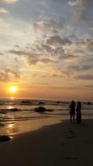 Two women watch the sunrise at huahin beach Thailand