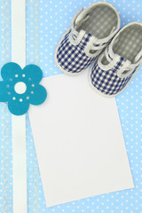 Baby shoes and blank card on blue polka background