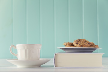 A coffee and some chocolate chip cookies over a book. Vintage
