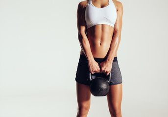Young woman in sportswear holding a kettle bell