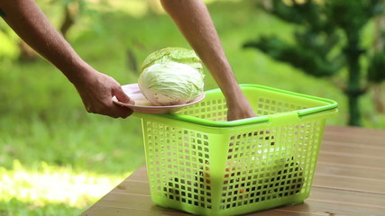man chooses from a basket plate of cabbage for cooking borch