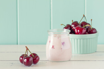 A jar with cherry yogurt and some cherries in a turquoise bowl.