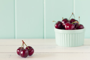 Cherries in a whiteware baking bowl on a white wooden table.
