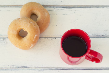 Two donuts (Doughnut) and a cup of coffee on a white table.